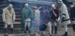 Reenactors try to stay warm outside soldier huts in Jockey Hollow