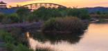 A tree-lined river, bridge in the distance, and the backdrop of a colorful, pastel evening sky.
