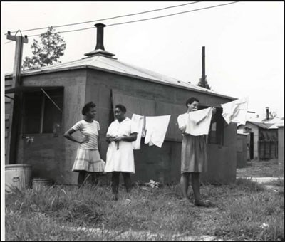 3 women stand next to a clothes line