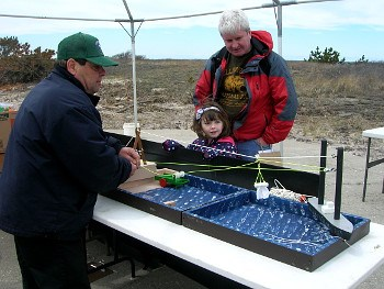 Park volunteer demonstrating beach apparatus to father and daughter