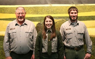 Three park rangers in front of exhibit