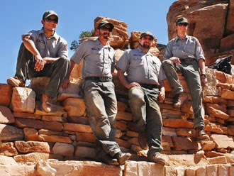 Four trail crew members sitting on rock wall