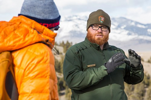 Male park ranger talking to visitor in mountain landscape