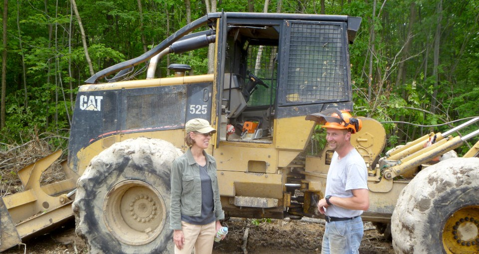 Man and woman talking in front of backhoe