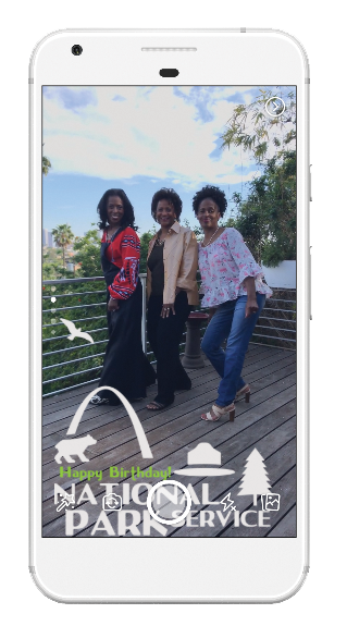 a smartphone displays a photo of three women outside with an overlay that says Happy Birthday National Park Service.