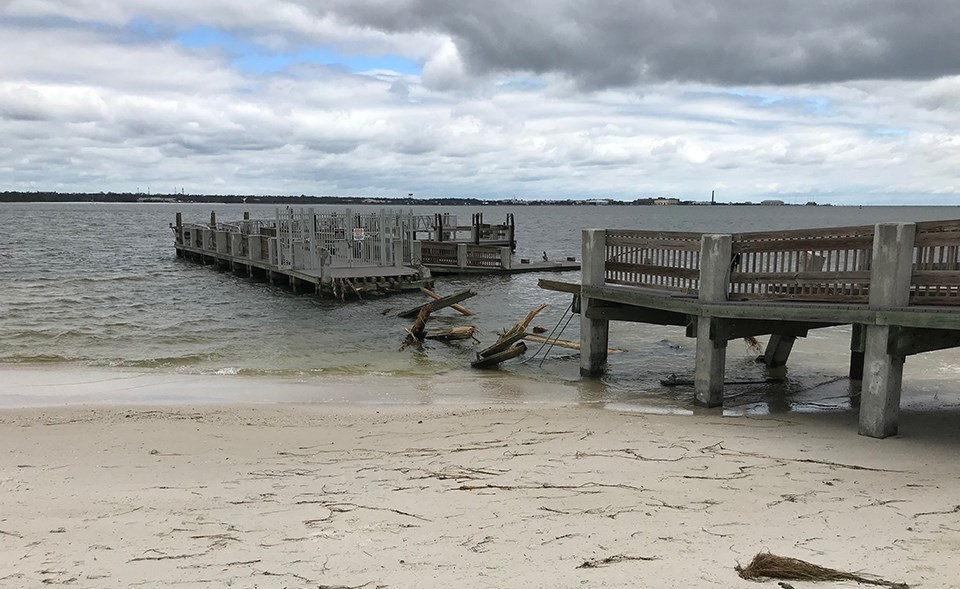 sections of a destroyed pier along a sandy beach