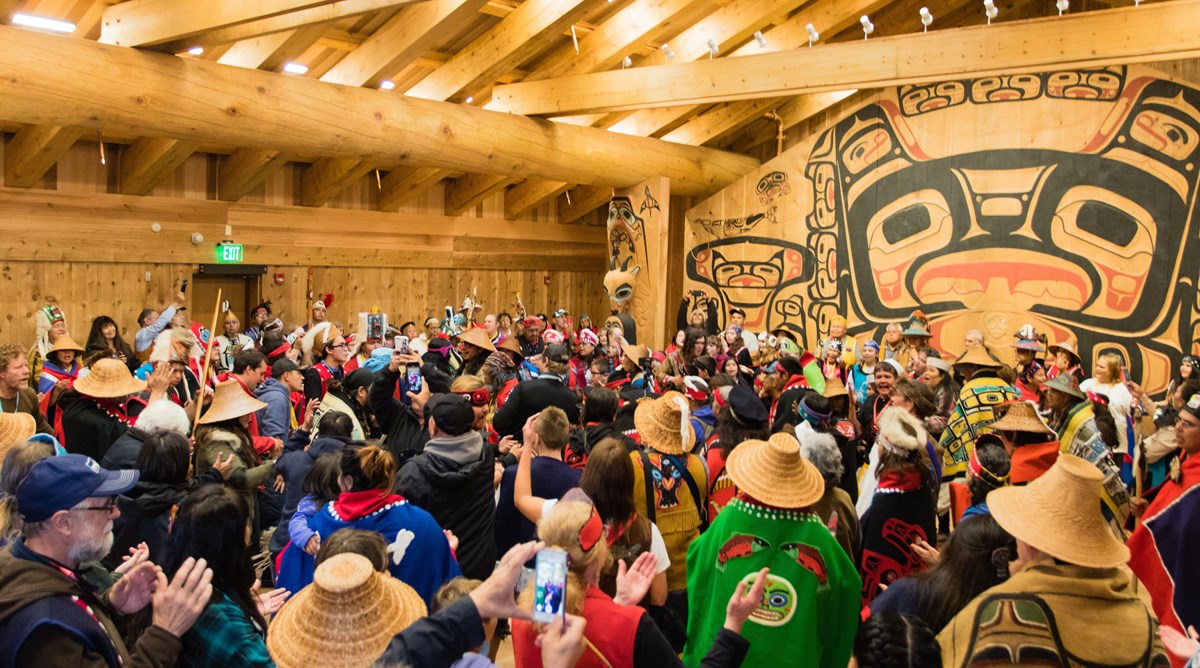 Large crowd gathered inside a wooden building with Huna Tlingit artwork on the walls