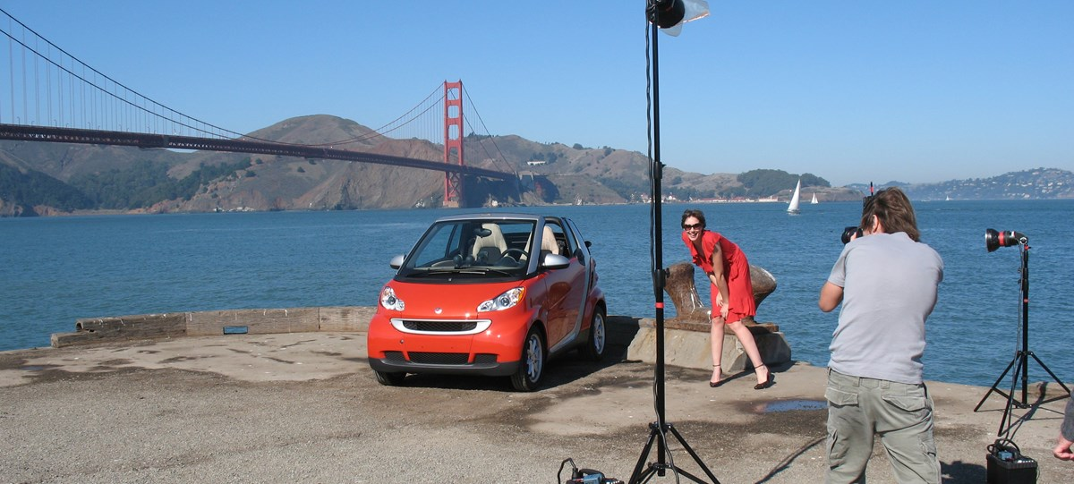 Photographer with a professional setup taking pictures of a model and car with the Golden Gate Bridge in the background