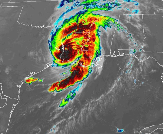 infrared satellite image showing shades of black, red, yellow, and blue swirling above a map of Texas and Louisiana