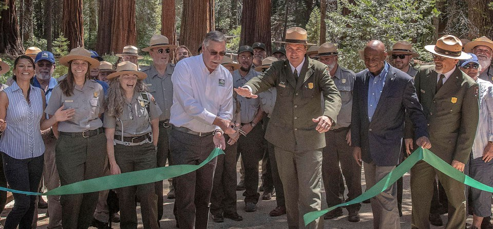 NPS uniformed rangers and partners cutting a large green ribbon in front of large trees