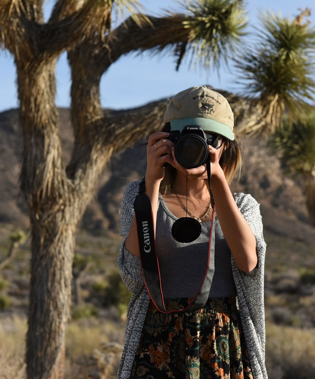a photographer standing in front of joshua trees holds a camera to her eye