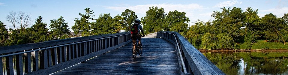 Bicyclist riding across a bridge over a channel