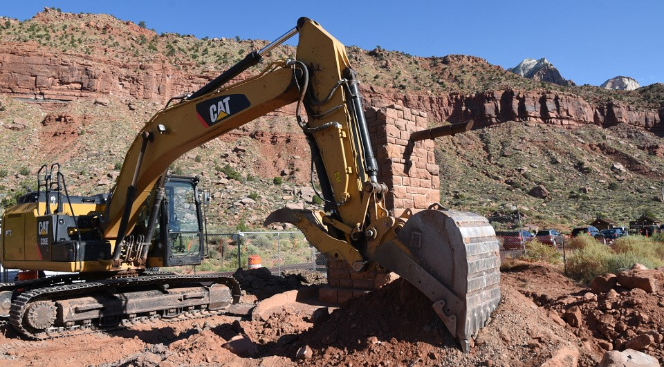 Backhoe digging up ground in national park