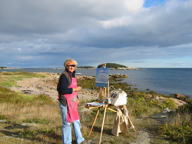 Photograph of artist Priscilla Whitlock on the coastline with her easel