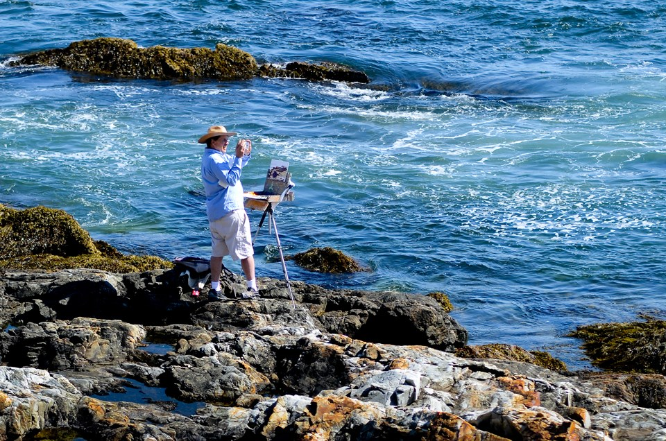 Painter with small easel works by open ocean