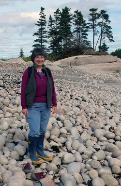 Woman standing on large shoreline rocks with tall trees in background