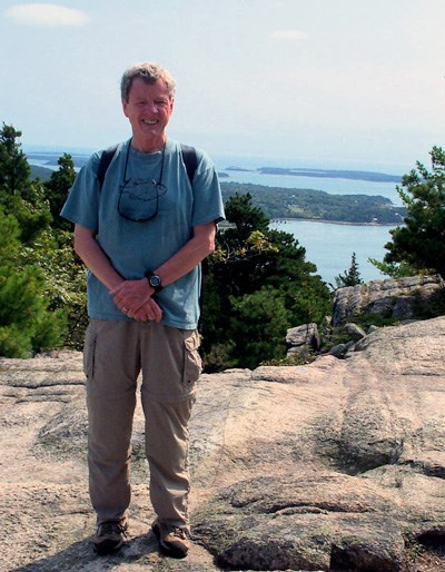 Man in T-shirt and cargo hiking pants poses with a backdrop of distant islands