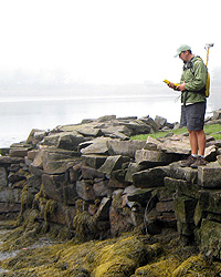 Man stands on rocky shore with GPS unit.
