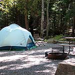 Tent, fire ring, and picnic table in campsite