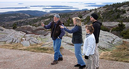 Four people stand on a trail on a mountain using a global positioning system unit.