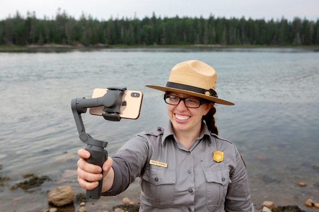 Park ranger stands on a beach while recording herself with a smartphone