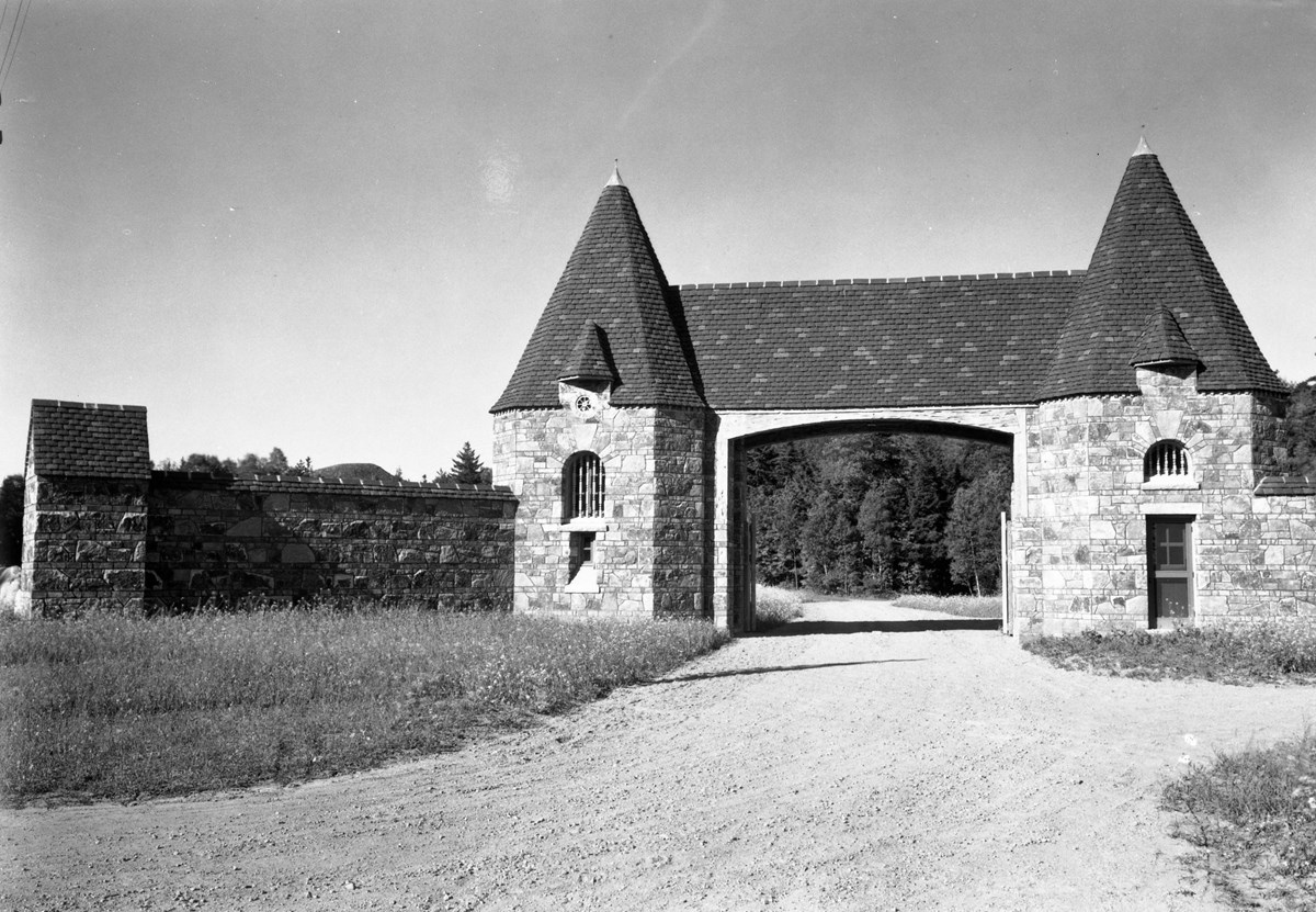 Stone gate and wall in front of a gravel road