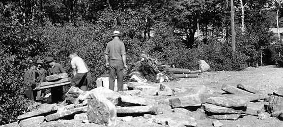Five men haul granite blocks.