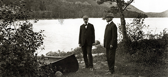 Two men stand near a canoe at the side of a lake.