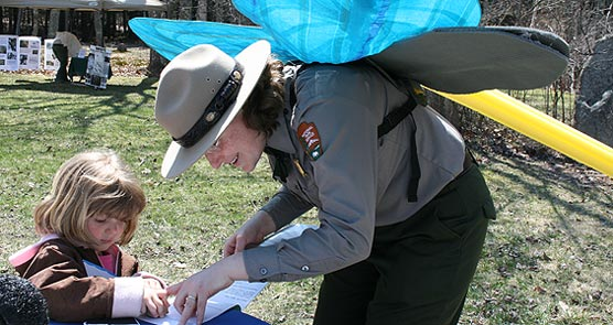 Park rangers wearing model dragonfly wings stamps child's book