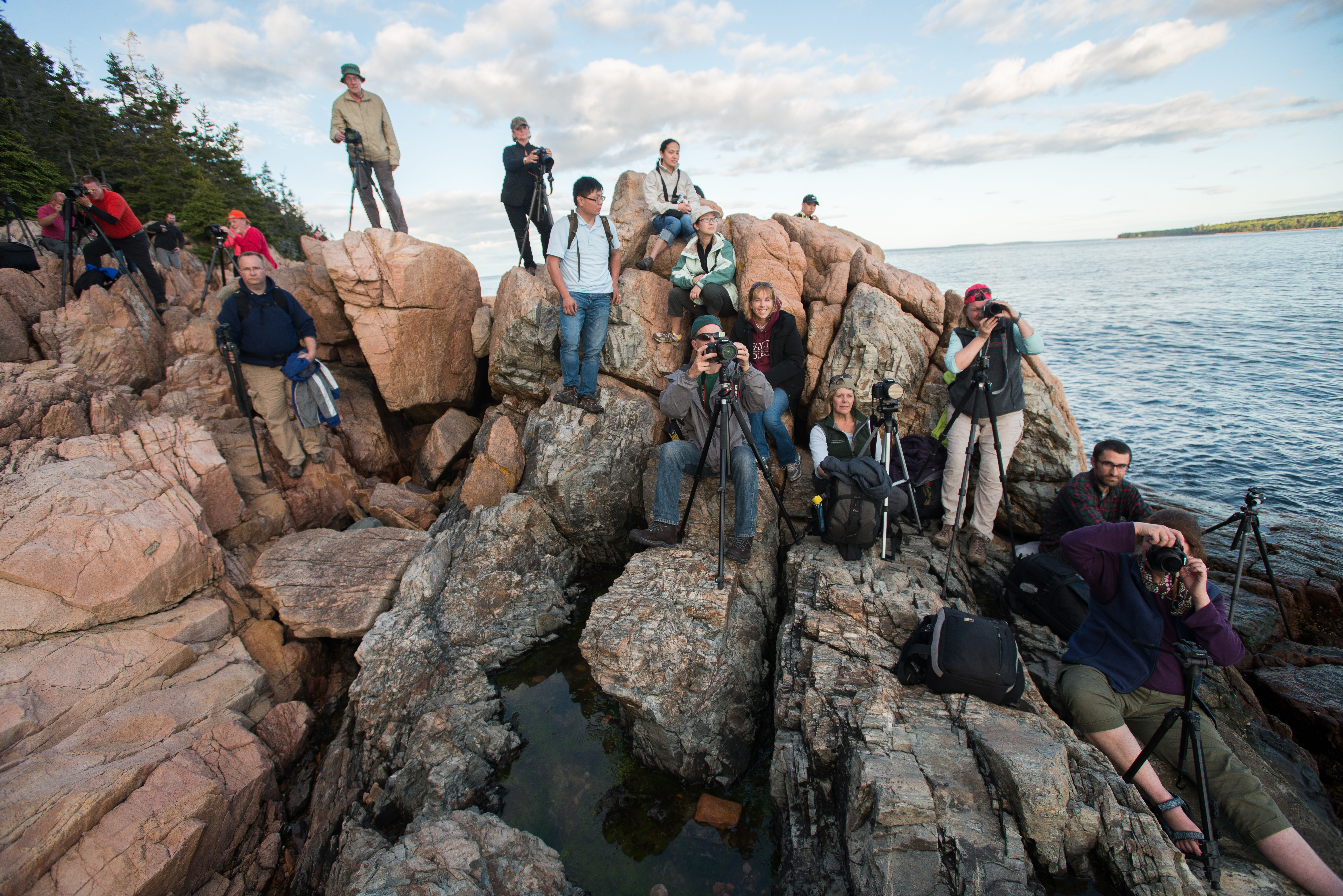 Dozens of photographers position themselves along a rocky shoreline