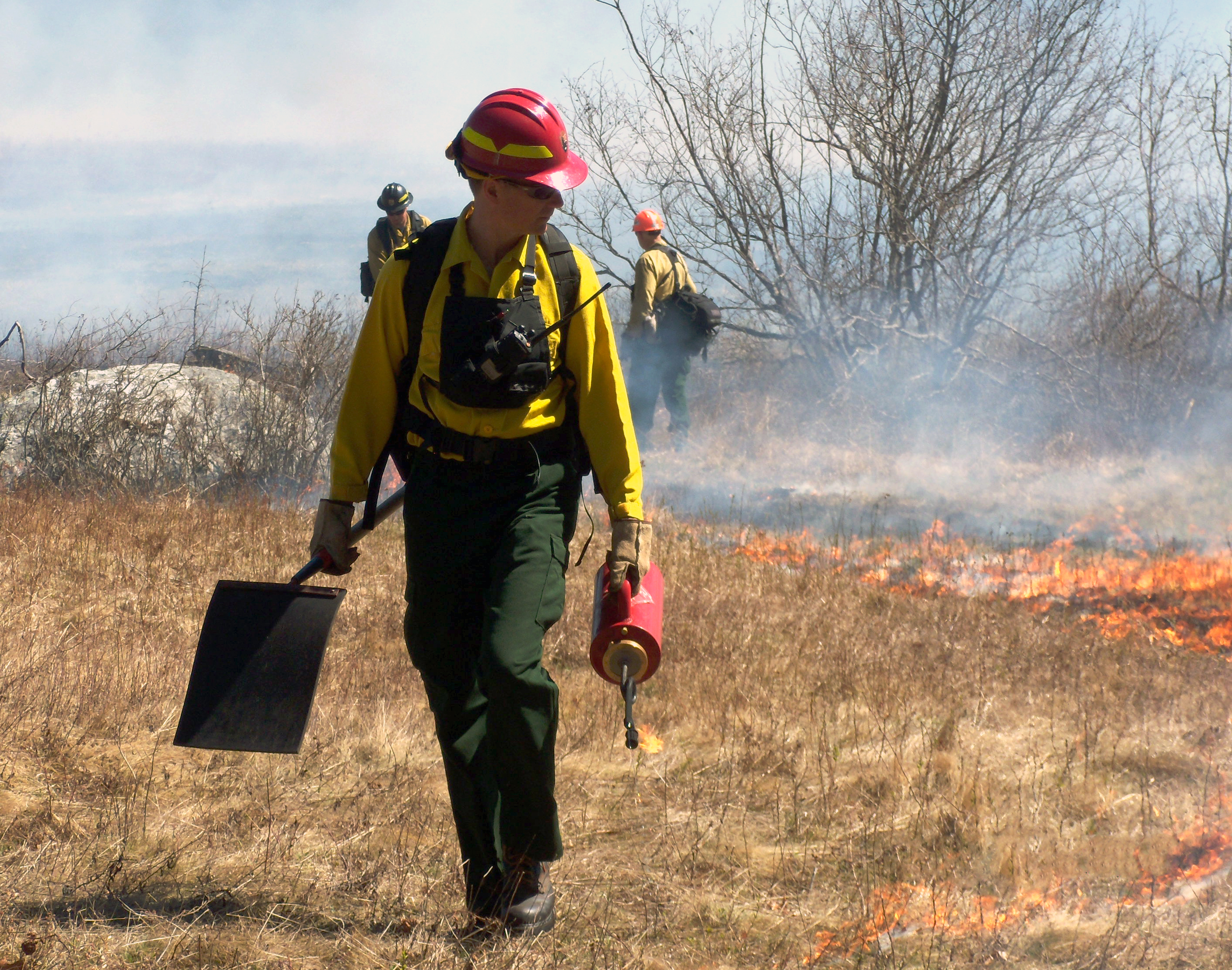 Willdland firefighter carries a drip torch