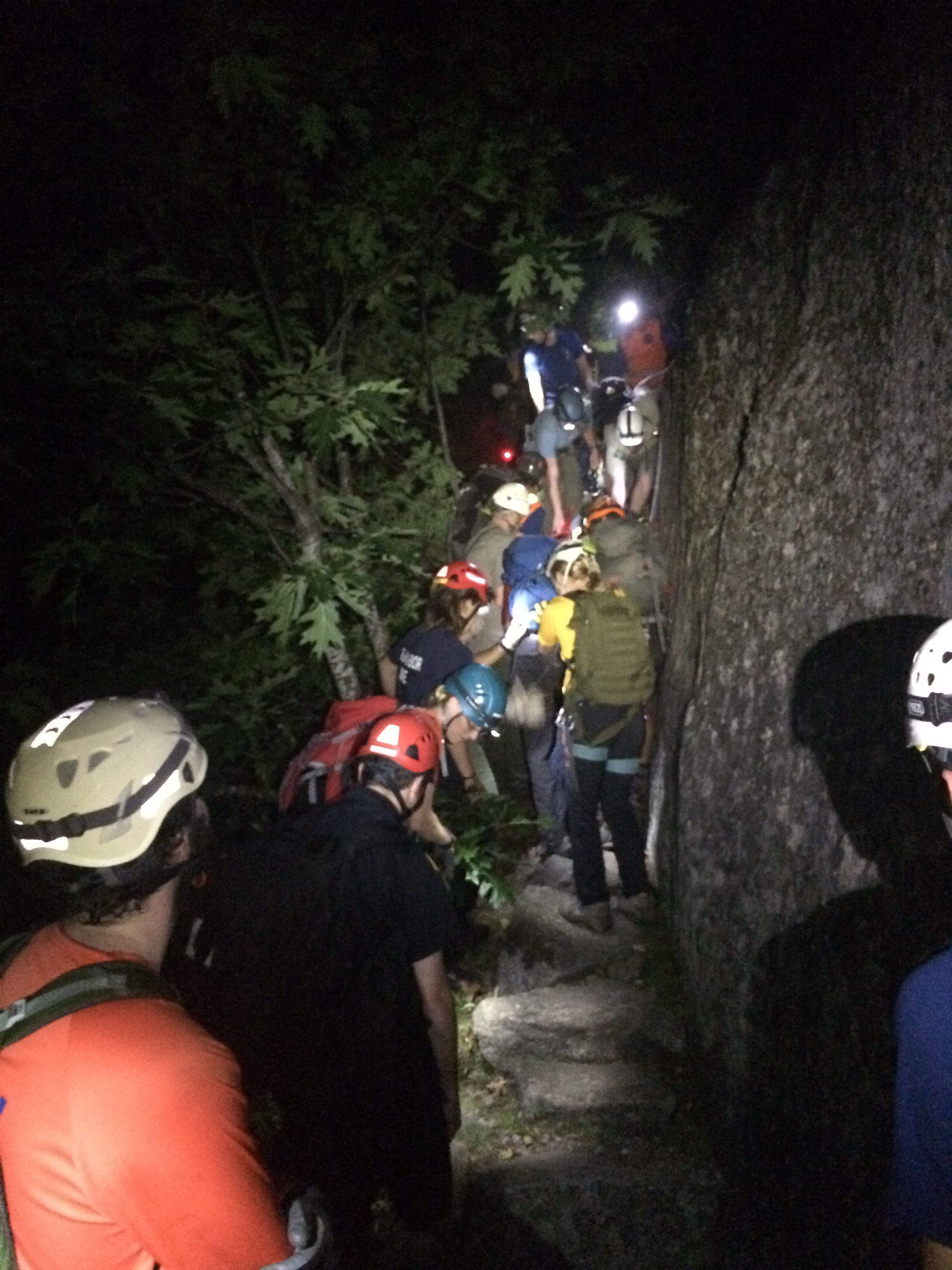 Rescuers on narrow trail along steep rock face