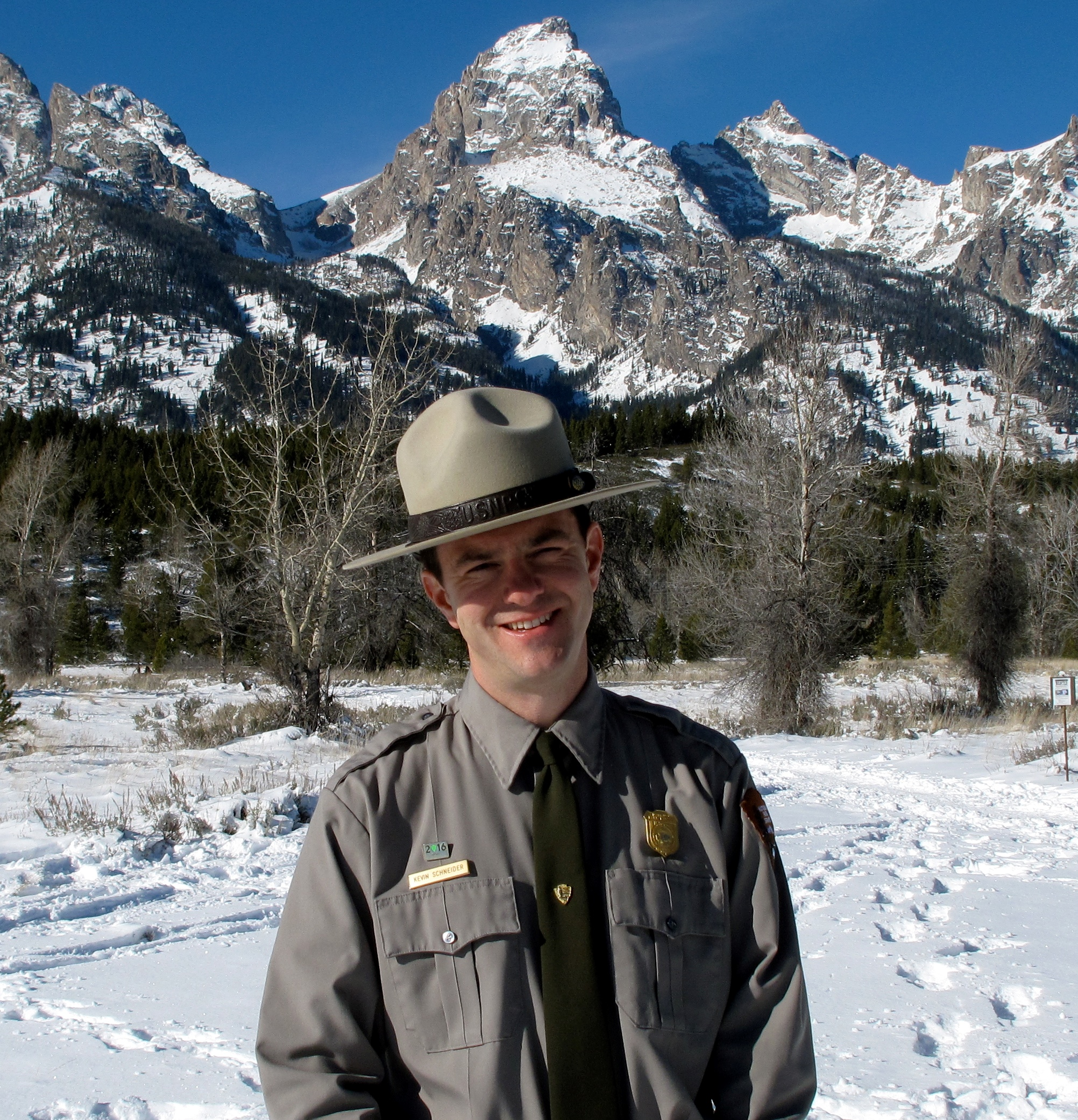 A man wearing a ranger uniform standing in front of snow covered rocky mountain peaks.