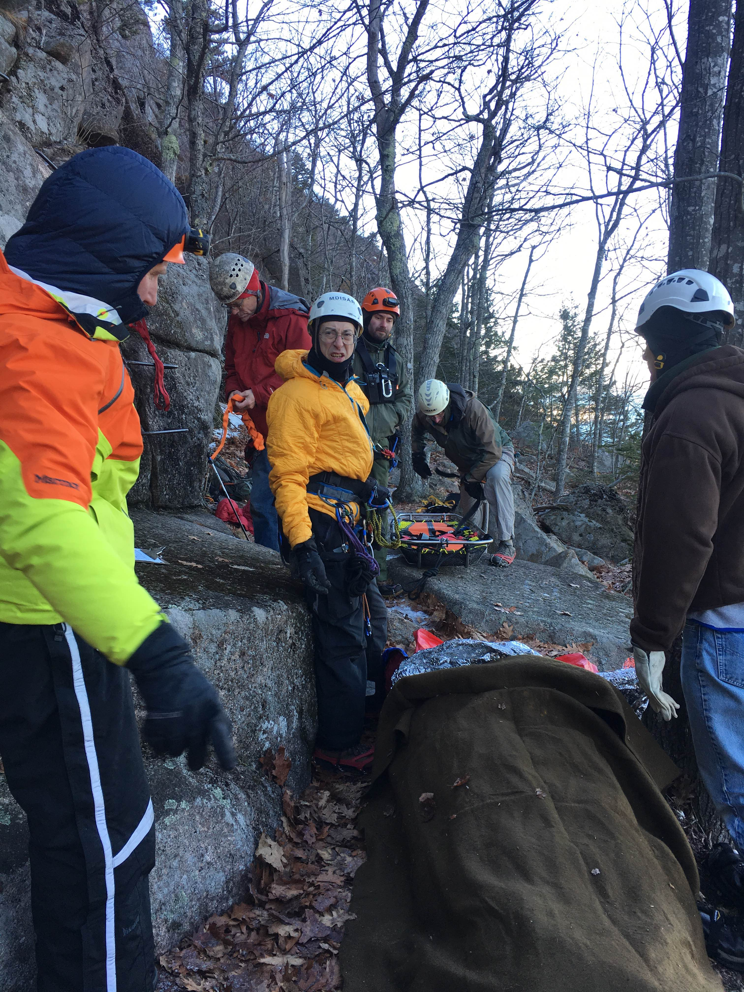 Park rangers and volunteers from Mount Desert Island Search and Rescue prepare to hoist patient by litter to the Maine Army National Guard helicopter.
