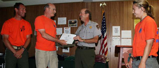 Three volunteers accept an award from the park superintendent.