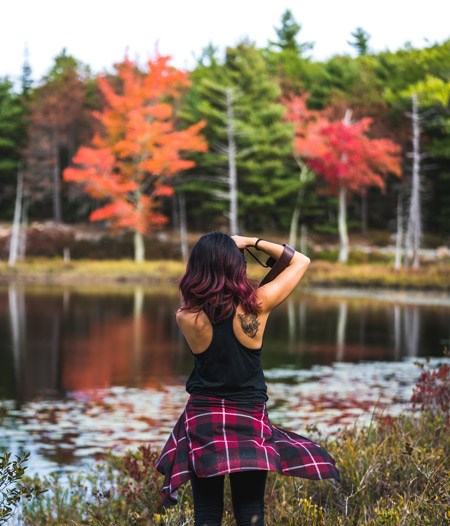 Woman takes a photograph by pond saturated in fall colors