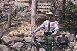 Park ranger with bike stands near carriage road sign.