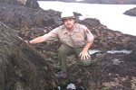 Park ranger crouches at the side of a tidepool.