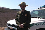 Park ranger stands outside vehicle.