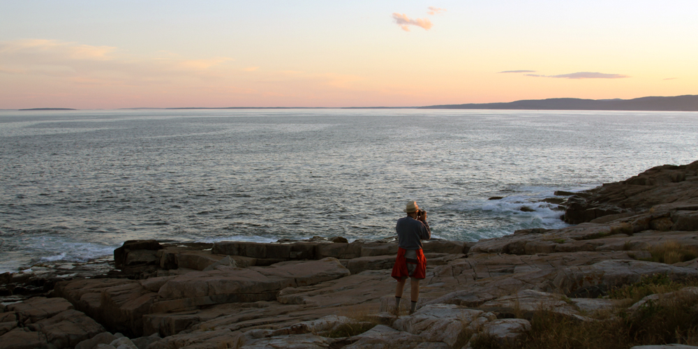 A visitor photographs the sunset along the Schoodic Peninsula shoreline.