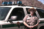 Park ranger stands outside park vehicle.