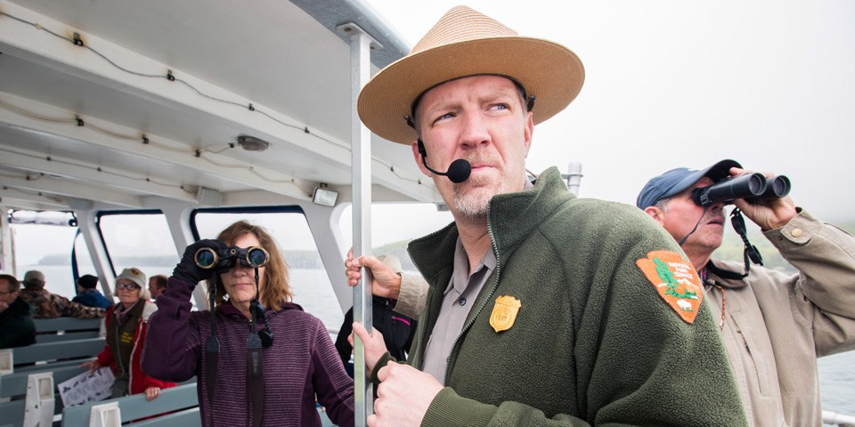 Ranger on boat looks into distance while two visitors look through binoculars