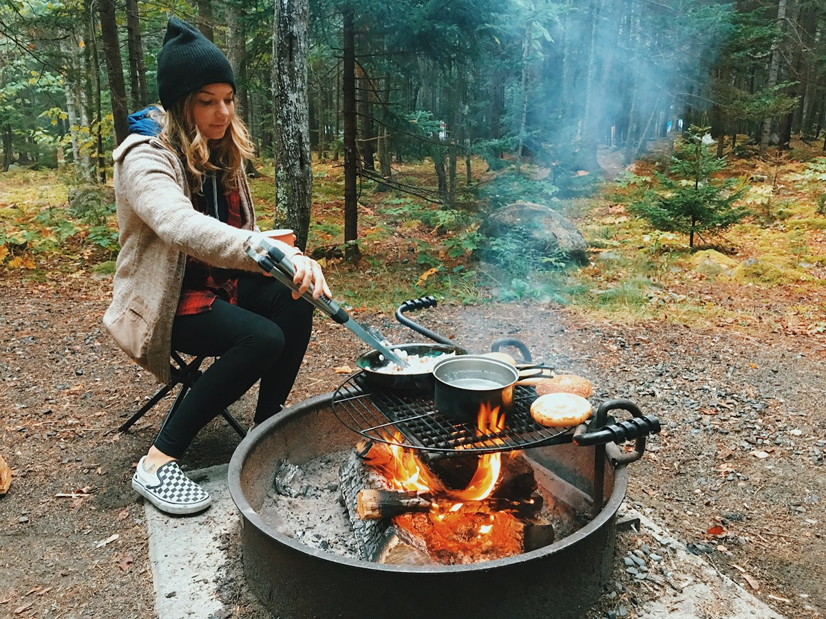 Woman makes breakfast on a campfire in a park campground