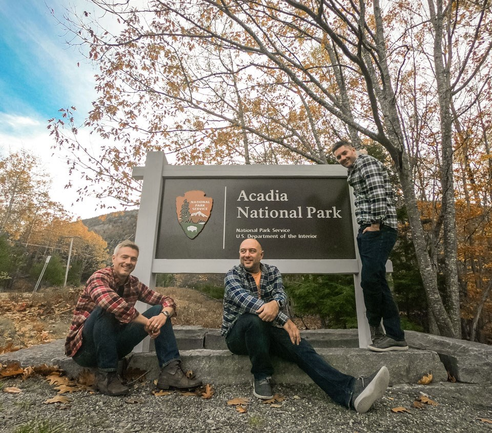 Three men wearing flannel shirts pose by Acadia park sign