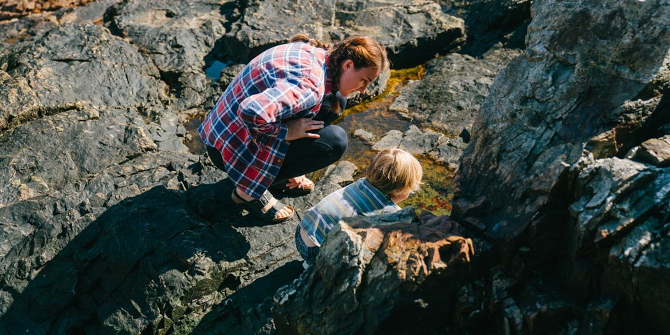 Woman and child crouch to explore among rocks