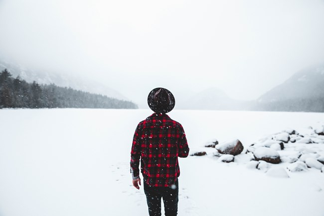 Man in hat and red plaid jacket looks across frozen lake as snow falls