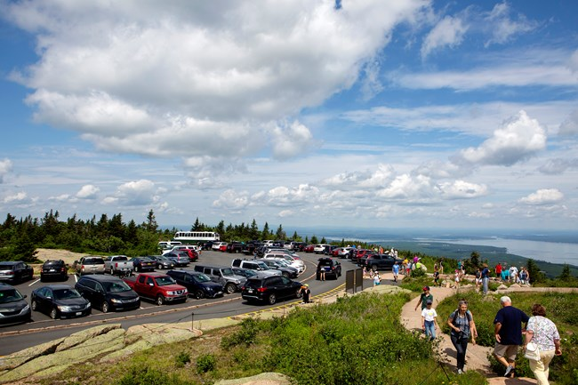 Congested parking area and trail on a mountain summit