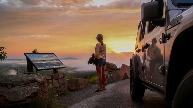 Woman watches sunset standing between a jeep and a park wayside