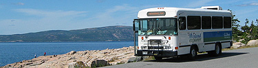 An Island Explorer bus waits to pick up passengers along the shoreline.