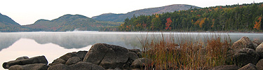 Glassy lake with rocks and grasses in foreground, fall colors in background